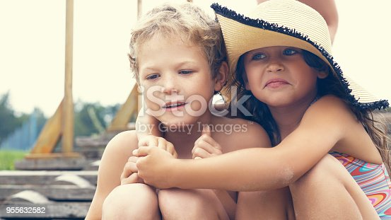 209e6da24a8 Portrait Of Children On The Beach In Summer Little Girl In A Hat Hugs Her  Brother They Are Sitting On The Stairs By The Sea Stock Photo   More  Pictures of ...