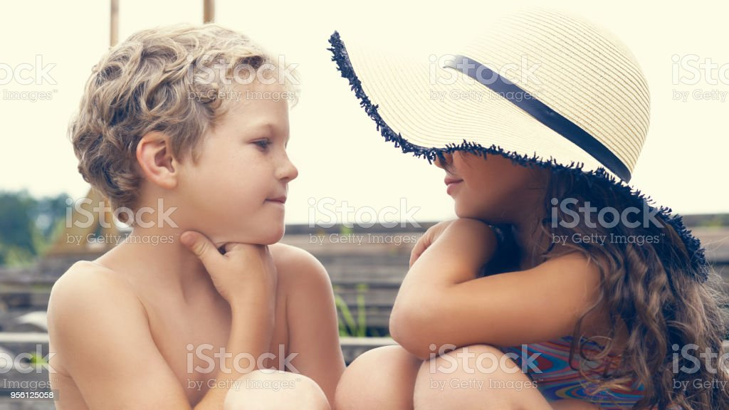 05f80cf9eb Portrait of children on the beach in summer. Little girl in a hat talking to