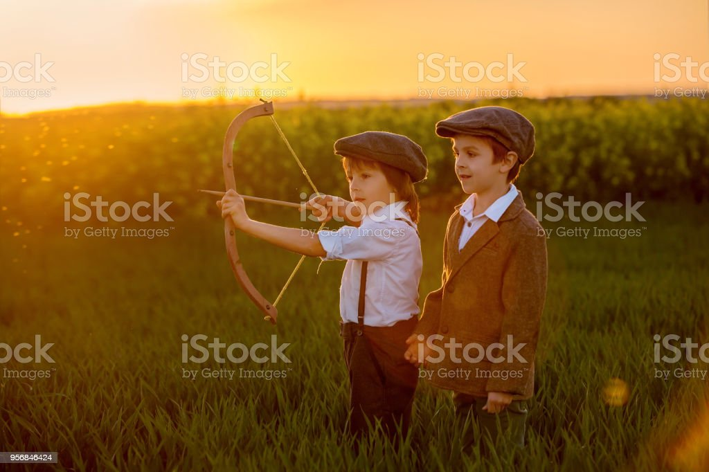 Portrait of children playing with bow and arrows, archery shoots a bow at the target stock photo