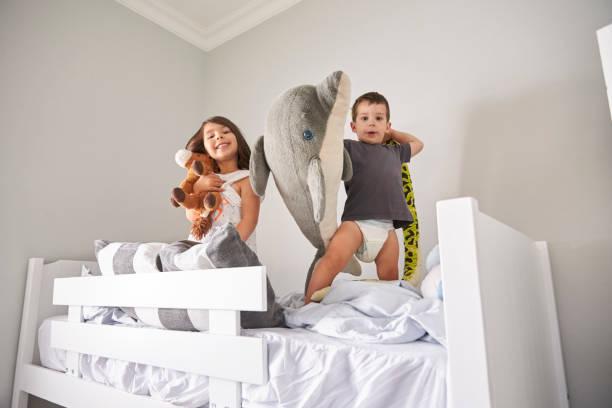 porträt von kindern spielen mit spielzeug im bett - etagenbett weiss stock-fotos und bilder