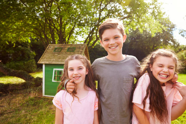 porträt von kindern stehen im garten neben playhouse - mädchen spielhaus stock-fotos und bilder