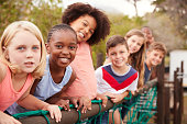 Portrait Of Children Standing On Rope Bridge With Friends In Park