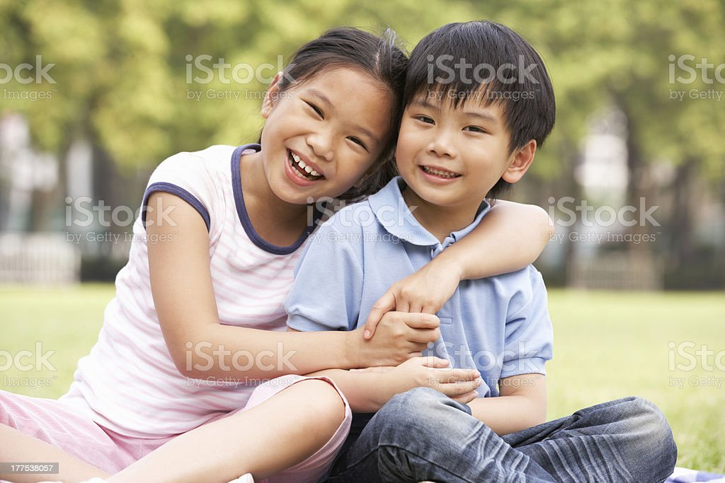 Portrait Of Chinese Boy And Girl Sitting In Park Together stock photo