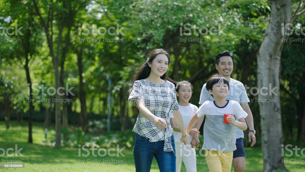 portrait of Chinese parents & kids walking outdoors & laughing stock photo
