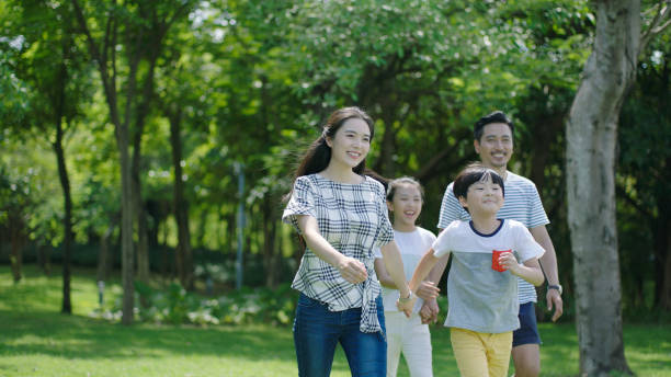 portrait of chinese parents & kids walking outdoors & laughing - singapore nature stock photos and pictures