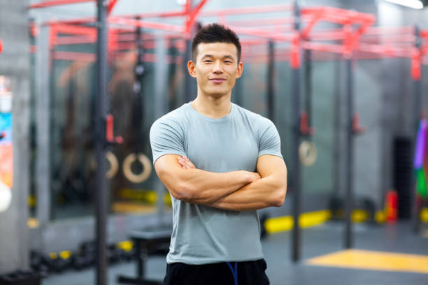 Portrait of Chinese personal trainer in gym stock photo