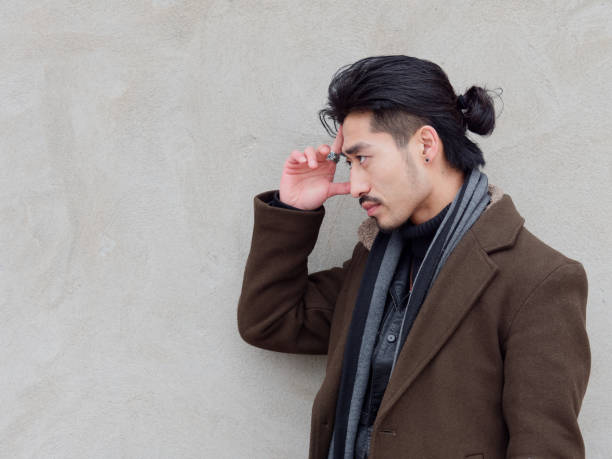 Portrait of Chinese young mustached man put his hand on his forehead with gray wall background, thinking, side view. stock photo