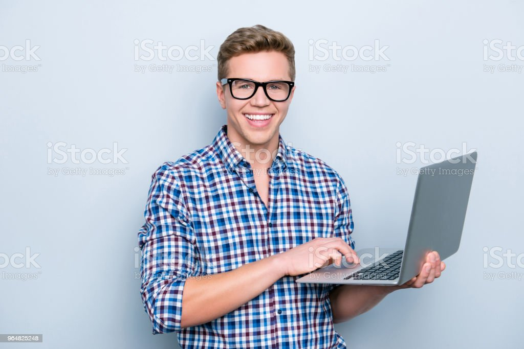 Portrait of clever cheerful confident focused smart educated intelligent excited teacher holding modern netbook in hands using it for checking information isolated on gray background copy-space royalty-free stock photo