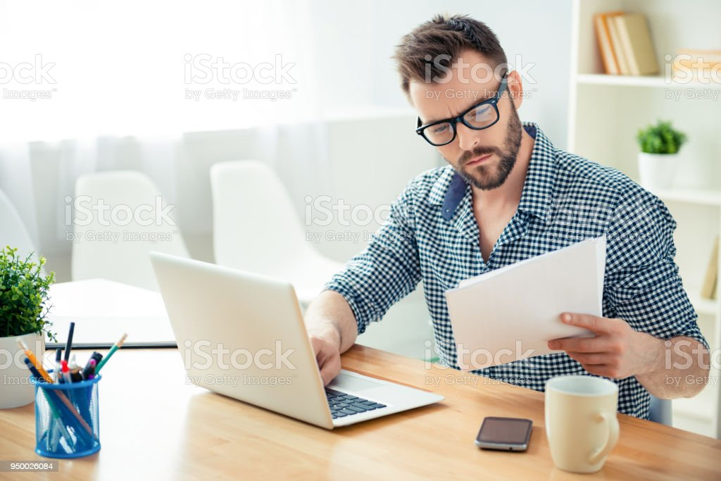 Portrait of concentrated businessman in glasses with laptop reading contract stock photo
