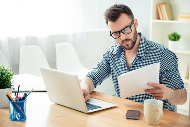 portrait of concentrated businessman in glasses with laptop reading contract - concentration stock photos and pictures