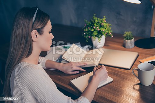 840623374 istock photo Portrait of concentrated busy girl using book writing down notes in notepad having pencil in hands preparing for presentation conference sitting in work place station. Level up concept 976592002