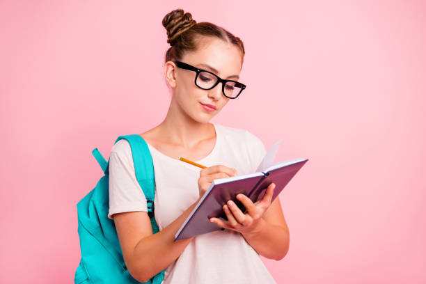 Portrait of concentrated reader student girl writes in notebook isolated on vivid pink background with copy space for text Portrait of concentrated reader student girl writes in notebook isolated on vivid pink background with copy space for text nerd hairstyles for girls stock pictures, royalty-free photos & images