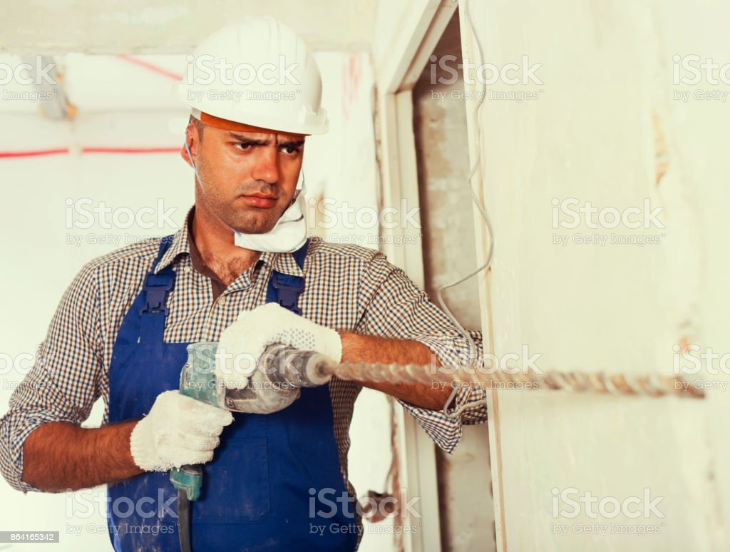 Portrait of concentrated repairer male standing with drill indoo royalty-free stock photo