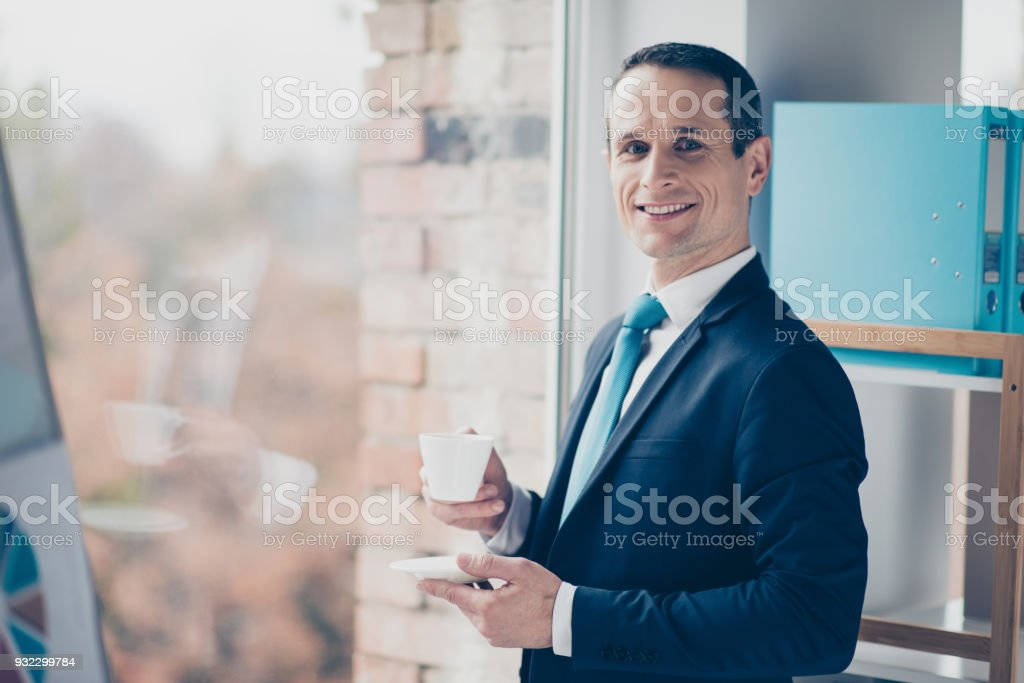 Portrait of concentrated rich successful wealthy fashionable modern qualified smart intelligent entrepreneur wearing classic suit and shirt holding aromatic fresh cup of coffee waiting for client stock photo