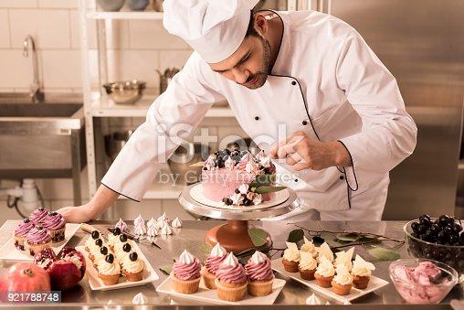 portrait of confectioner decorating cake in restaurant kitchen