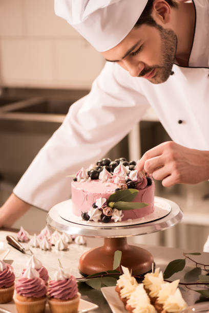portrait of confectioner decorating cake in restaurant kitchen portrait of confectioner decorating cake in restaurant kitchen decorating a cake stock pictures, royalty-free photos & images