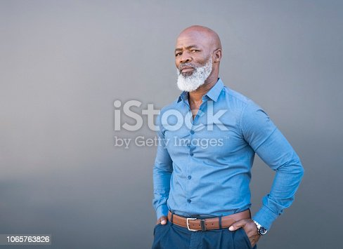 istock Portrait of confident African American male against gray wall 1065763826