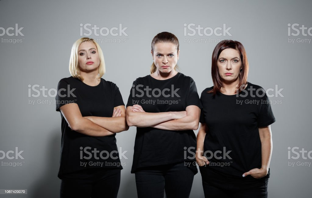 Portrait of confident and determinated women protesting Three displeased women wearing black clothes, standing with arms crossed against grey background, staring at camera. Studio shot. Activist Stock Photo