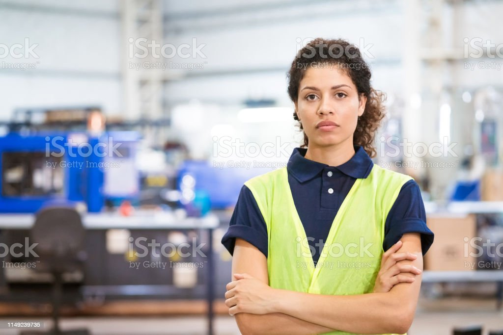 Portrait of confident apprentice with arms crossed Portrait of confident mid adult apprentice. Female engineer is standing with arms crossed. She is in reflective clothing. 30-34 Years Stock Photo