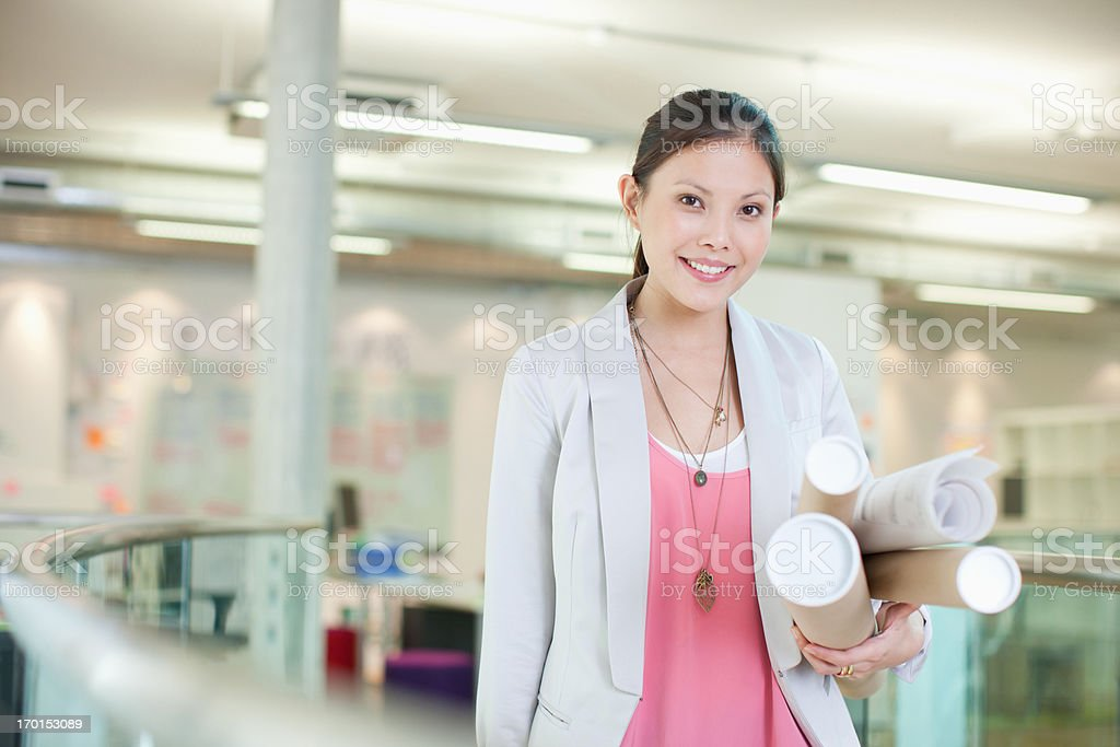 Portrait of confident architect holding blueprint tubes in office
