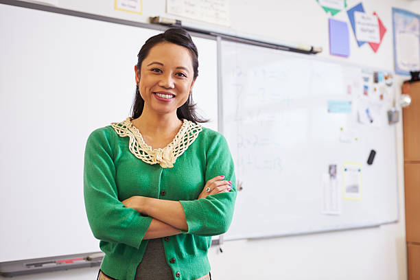 Portrait of confident Asian female teacher in classroom stock photo