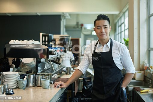 istock Portrait of confident barista standing at cafe 1125677508