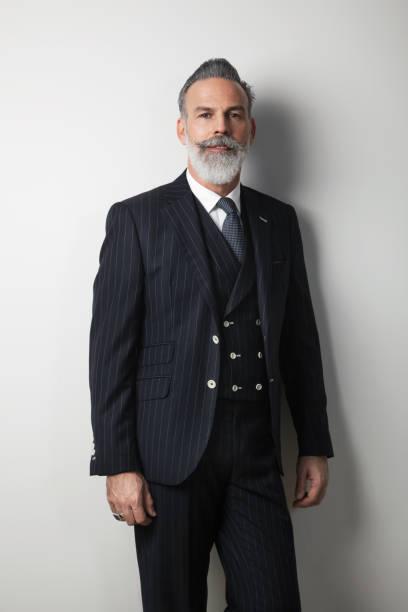 Porträt von zuversichtlich bärtigen Mitte im Alter Gentleman trendigen Anzug über leeren weißen Hintergrund. Studio gedreht. Vertikal – Foto