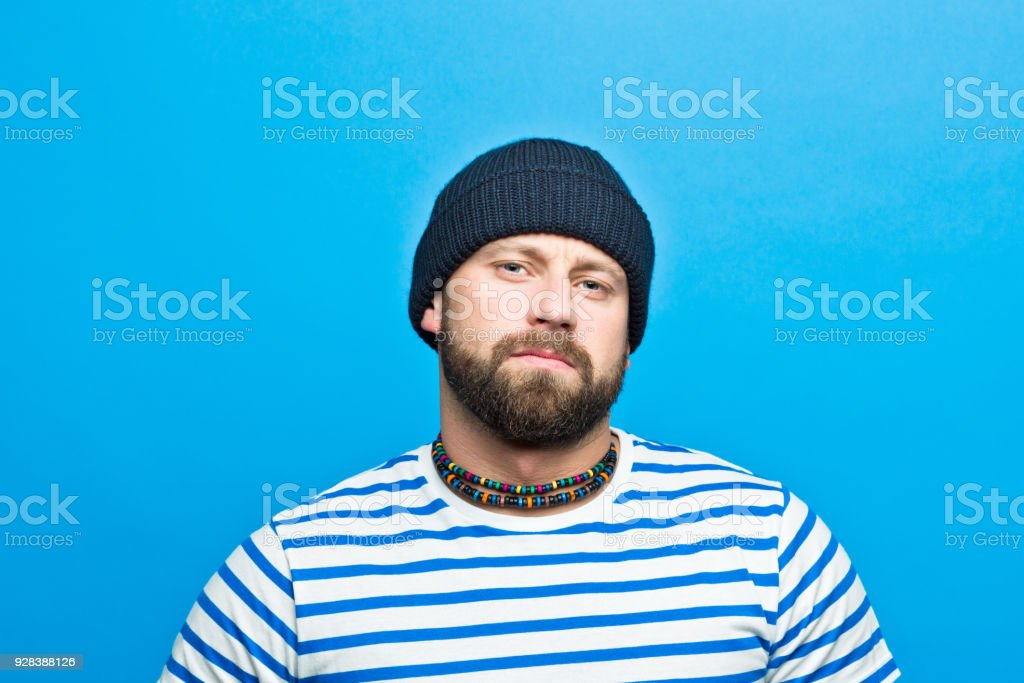 Portrait of confident bearded sailor against ble background Portrait of confident bearded man wearing striped t-shirt and beanie hat looking at camera. Studio shot, blue background. 30-34 Years Stock Photo