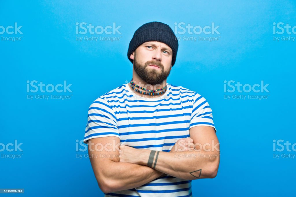 Portrait of confident bearded sailor against ble background Portrait of confident bearded man wearing striped t-shirt and beanie hat. Studio shot, blue background. 30-34 Years Stock Photo