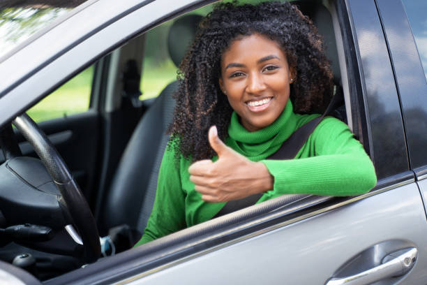 Portrait of confident black woman driving her new car stock photo