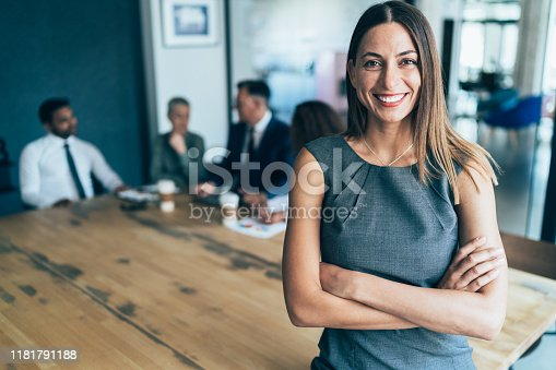 Portrait of confident beautiful business woman with arms crossed at the office with her team behind