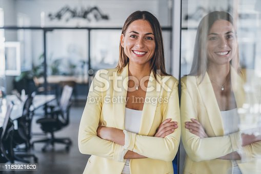 Portrait of confident beautiful business woman with arms crossed at the office