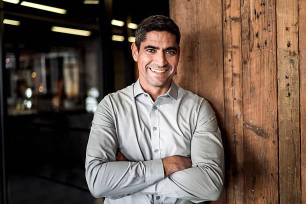 portrait of confident businessman against wooden wall - 30 39 jaar stockfoto's en -beelden