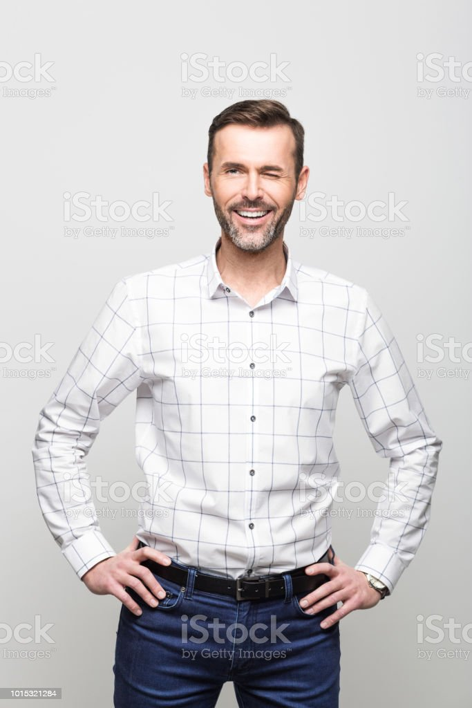 Portrait of confident businessman blinking at camera, grey background Portrait of handsome successful businessman wearing white shirt and jeans, smiling at the camera. Studio portrait, grey background. 30-39 Years Stock Photo