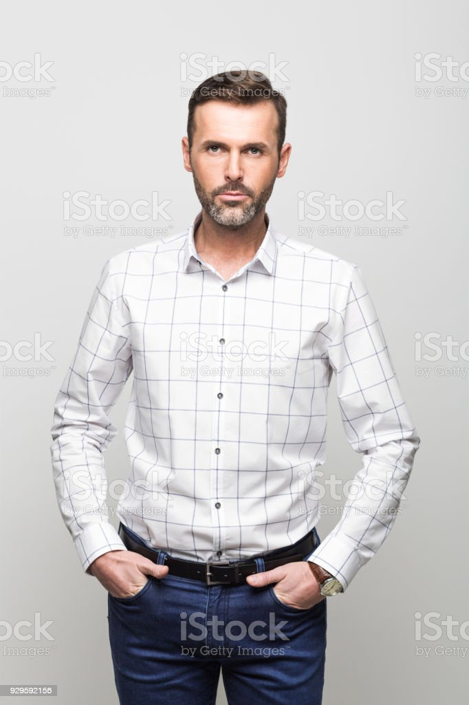 Portrait of confident businessman, grey background Portrait of confident businessman wearing white shirt and jeans, standing with hands in pockets, looking at the camera. Studio portrait, grey background. 30-39 Years Stock Photo