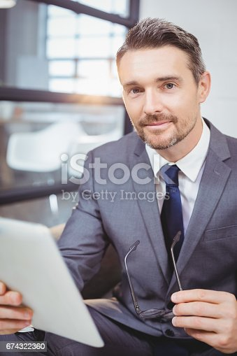 530281723istockphoto Portrait of confident businessman holding digital tablet while sitting on sofa 674322360