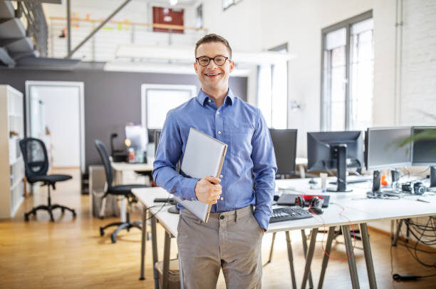 Portrait of confident businessman in office with a laptop stock photo