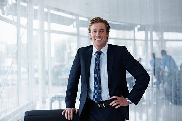 Portrait of confident businessman Portrait of confident businessman standing with hand on hip in office business suit stock pictures, royalty-free photos & images
