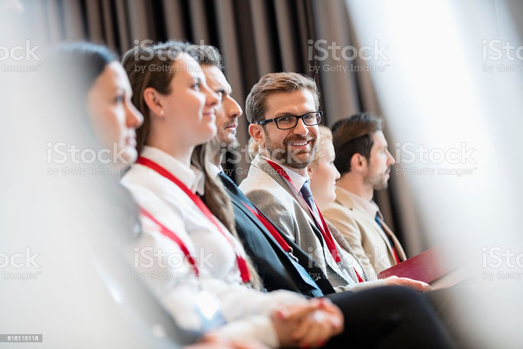 Portrait of confident businessman sitting in seminar hall stock photo