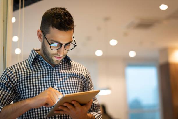 Retrato del empresario confiado uso de tableta en la oficina - foto de stock