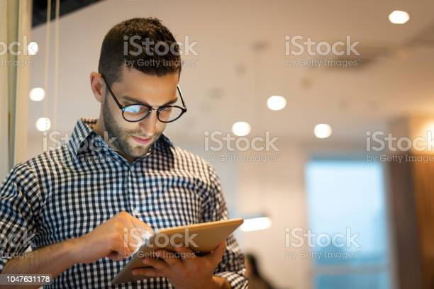 Portrait Of Confident Businessman Using Tablet At Office Stock Photo - Download Image Now