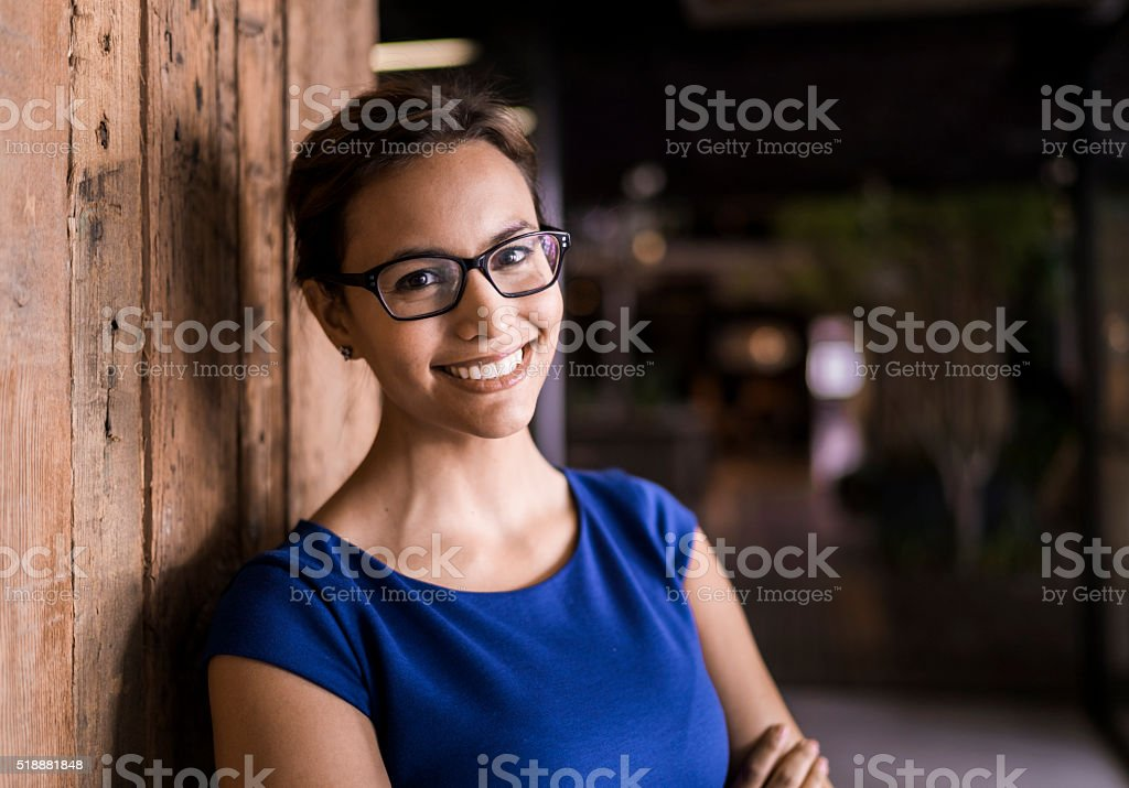 Portrait of confident businesswoman against wooden wall stock photo