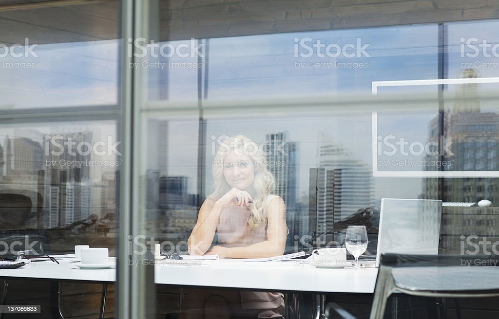 Portrait of confident businesswoman at table in conference room royalty-free stock photo