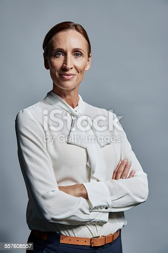 Portrait of confident mature businesswoman standing arms crossed over gray background