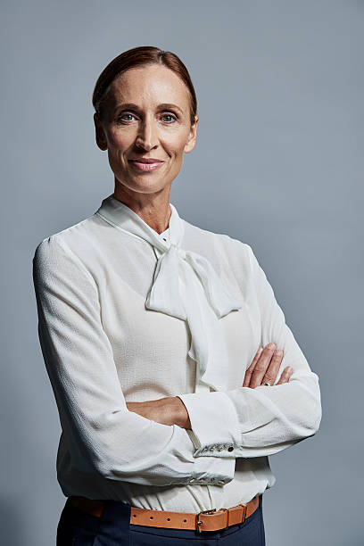 Portrait of confident businesswoman Portrait of confident mature businesswoman standing arms crossed over gray background blouse stock pictures, royalty-free photos & images