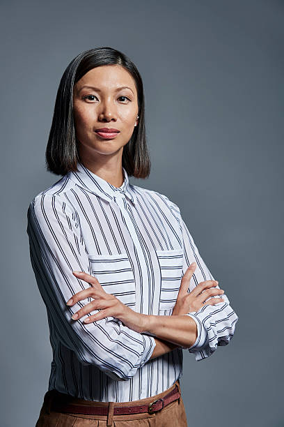 Portrait of confident businesswoman Portrait of confident businesswoman standing arms crossed over gray background waist up stock pictures, royalty-free photos & images