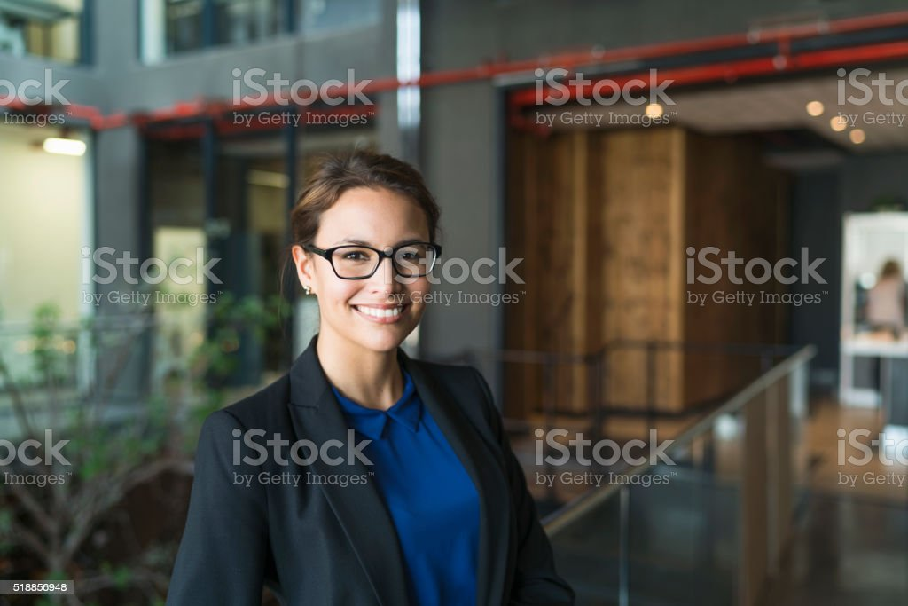 Portrait of confident businesswoman smiling in office stock photo