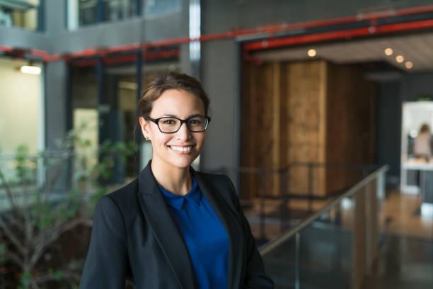 portrait of confident businesswoman smiling in office - 30 39 jaar stockfoto's en -beelden