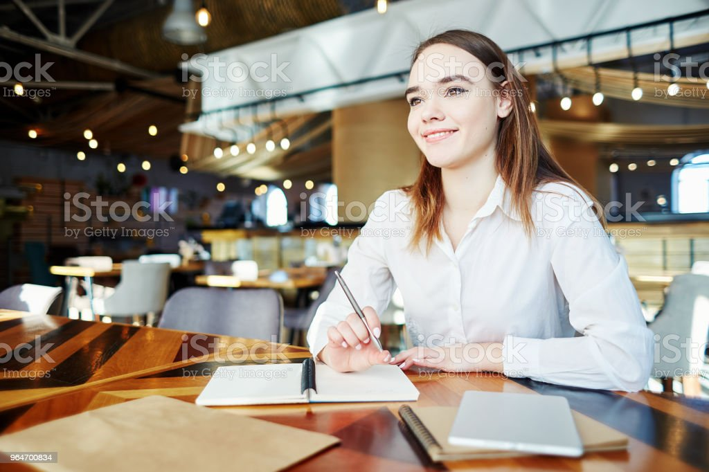 Portrait of confident businesswoman smiling while thinking of plans at cafe table royalty-free stock photo