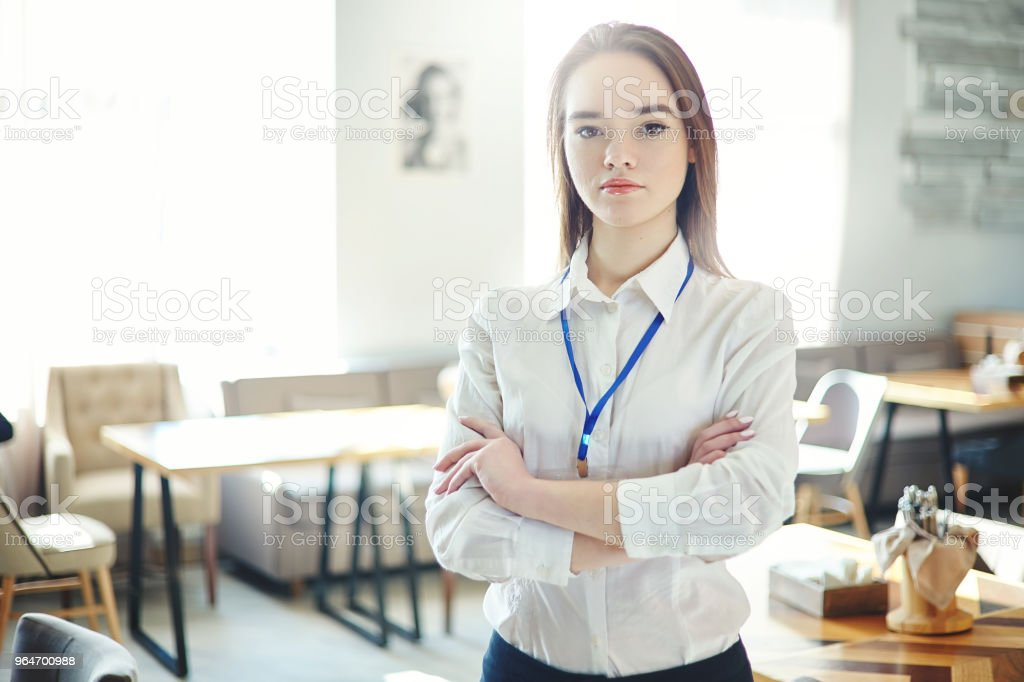 Portrait of confident businesswoman standing cross-armed and looking at camera, id card around her neck royalty-free stock photo